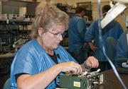 Assembly associate Darcy Berkel puts the finishing touches on one of the AN/PRC-155 Manpack Radios in the radio production area at General Dynamics C4 Systems' Scottsdale headquarters.