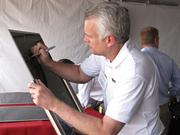 William Fehrman, president and CEO of MidAmerican Energy Co., signs a solar panel commemorating the first 100 megawatts of power production at the Agua Caliente solar project outside Yuma. MidAmerican is a minority investor in the project.
