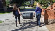 ASU students Lindsay Fleming, left, and Taylor Barker carry a water filter barrel they made to help people in South Africa.