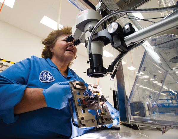 JoAnne Castillo inspects a lens she installed in a component used in GE's ultrasound probes manufactured in east Phoenix. GE Global Ultrasound Probes recently received U.S. Food and Drug Administration approval for a device that allows patients to receive an ultrasound scan from inside the body during a procedure.
