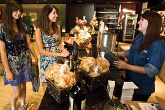 """Rachel Massey serves Kelsey Collier, left, and Michelle Anderson at the iPic Theatre in Scottsdale, one of a several new movie venues in the Valley that are enticing patrons with amenities such as a """"grab and go"""" menu, martinis and buckets of beer."""