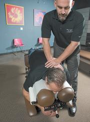 Dr. Kevin Lees adjusts a client of The Joint franchise at 16th Street and Camelback Road.