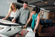 Emily Ginzl, left, Gary Serviss and Melanie McBride of E.B. Lane survey story boards for a TV ad. The Phoenix agency is looking to snag a larger share of the Hispanic market.