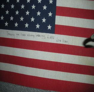 """One of five flags placed at the crash site of United Flight 93 by the family of passenger Thomas Burnett. The inscription reads, """"Tommy you have always been my HERO. Love Mom."""" It is on display as part of a flag exhibit, Stars & Stripes: An American Story, that opened Saturday morning and runs through Flag Day in June."""