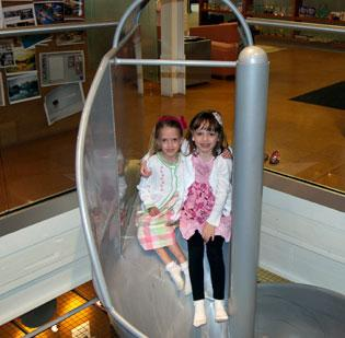 Katie Rose Rankin, 6, and Chloe Smith, 6, become fast friends as they make their way down to the second floor using the SBA spiral slide at Smith Brothers Agency on Take Your Sons and Daughters to Work Day.