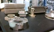 Examples of parts that were made using additive manufacturing at ExOne. Using the company's latest machine a layer of material can be placed in 30 seconds. The round part in the front of the picture is about 300 layers.