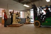 TechShop workers placing a vertical lathe in the milling space at the Bakery Square facility.