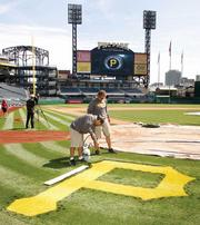 Members of PNC Park's grounds crew paint a logo on the grass behind home plate April 3, 2012, in preparation for Thursday's home opener against the Philadelphia Phillies.