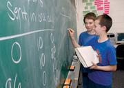 Brentwood Middle School seventh-graders Michael Lane, front, and Luke Gidias attempt to solve a problem in Lynne Golvash's pre-algebra class. The school is in the Brentwood Borough School District, which ranked No. 40 on the honor roll list of local public districts.