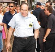 """Jack Cohen, owner of S.W. Randall Toys in downtown Pittsburgh, sports a vintage logo Batman button as he makes his way into the private screening of """"The Dark Knight Rises."""""""