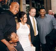 """Former Pittsburgh Steelers Hines Ward, far left, and Jerome Bettis, far right, stand with Thomas Tull, a minority owner of the Steelers and a producer on the film, before the private screening of """"The Dark Knight Rises"""" July 17, 2012, at the Byham Theater in downtown Pittsburgh."""