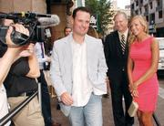 """Pittsburgh Mayor Luke Ravenstahl, left, makes his way past reporters and photographers as he heads into the private screening of """"The Dark Knight Rises"""" July 17, 2012, at the Byham Theater."""