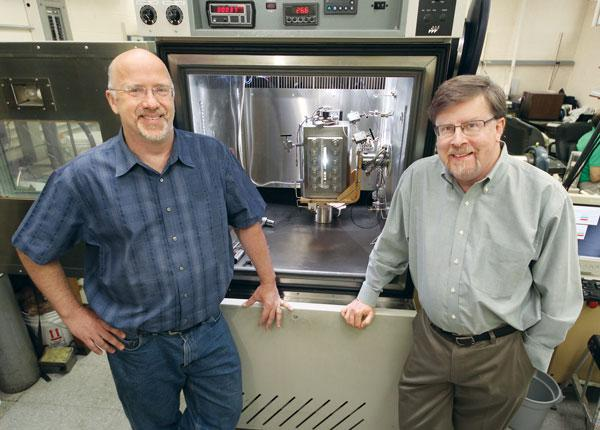 Robert Enick and Eric Beckman, researchers and professors at the University of Pittsburgh, flank a high-pressure cell used to determine if a thickener will dissolve and thicken in carbon dioxide.