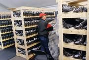 Magic Ice USA general manager Rosstyn Gudino removes plastic from a rack of rental skates at Penguins Pond at SouthSide Works.