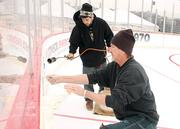 Palmer Products Imaging employees Dave Cramer, front, and Ryan Palmer remove old dasher board decals before applying new ones at Penguins Pond at SouthSide Works on Thursday.