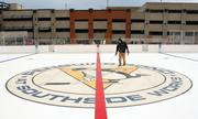 Rink Specialists employee Joshua Gilliam sprays water on the center ice logo to bond it to the surface at Penguins Pond.