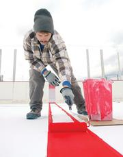 Rink Specialists employee Shaun Norris finishes painting the center ice line at Penguins Pond.