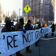 "Occupy Pittsburgh protesters take their ""We're not going anywhere"" sign closer to BNY Mellon's entrance Monday."