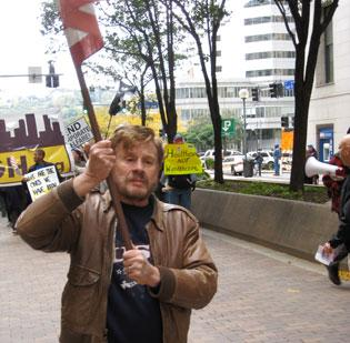 Ed Denslow leads the Occupy Pittsburgh parade with a U.S. flag as it moves through Pittsburgh on Saturday. As many as 3,500 marchers protested corporate greed, transit cuts and other concerns.