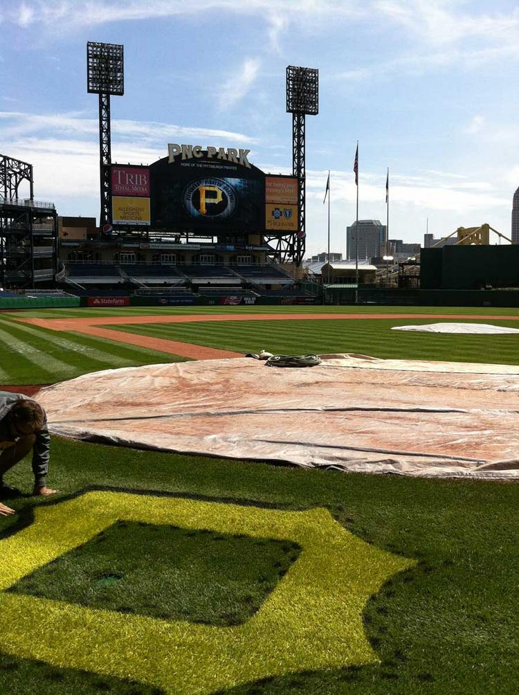 """Derek Hurlburt, a member of the grounds crew at PNC Park, works on the Pittsburgh Pirates' iconic """"P"""" in front of home plate on Tuesday ahead of Thursday's home opener against the Philadelphia Phillies."""