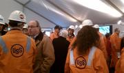 The dress code was bright orange and hard hat. At the center, U.S. Steel Chairman and CEO John Surma talks with Caren Glotfelty, director of the environment program at the Heinz Endowments. U.S. Steel and the Heinz Endowments are part of the Breathe Project.