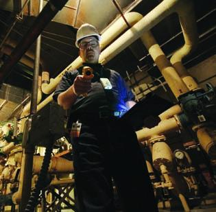 Ken Bowser, an efficiency agent for The Efficiency Network, uses an infrared thermometer to check the surface temperature of hot water pipes at the United Steelworkers Building, downtown. The Efficiency Network is assessing the cost of energy upgrades at the building for the United Steelworkers Union.