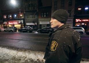 An off-duty Pittsburgh Police officer hired by a South Side bar to do private security watches the action on the 1300 block of East Carson Street.