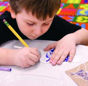 Cornell kindergartner Dominic DeAngelis attempts to write on tissue paper during a classroom project where students were directed to write on various types of papers.
