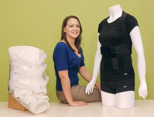 Kelly Collier, CEO and founder of ActivAided Orthotics, stands with the company's rehabilitative garment, right, for low back pain. The product is intended to be an alternative to another manufacturer's commonly used device, shown at left. Collier is deve