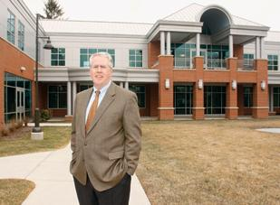 Jay Carson, senior vice president for institutional advancement at Robert Morris University, stands in front of the School of Business Building, which opened in September and is the first building that the university financed entirely through donations.