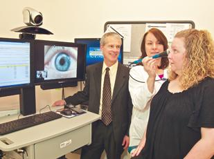 C. Leonard Eisenbeis, director of clinical health operations for UPMC WorkPartners, watches as Kathleen Vogelsberger and Heather Spiegel demonstrate a feature of the telemedicine system available at their Chatham Center clinic.