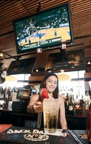College basketball plays on a television at Jerome Bettis Grille 36 on the North Side as bartender Tiffany Welsh pours a lunchtime drink.