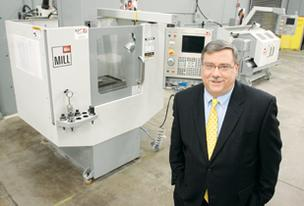 Jack Highfield, director of the Parkway West Career and Technology Center, stands near computer numerical control machines in the Oakdale school's robotics and precision machining shop.