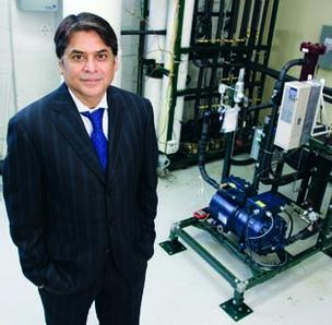 Lalit Chordia, president of Thar Energy, stands near a CO2 compressor that provides energy to heat and cool the company's building.