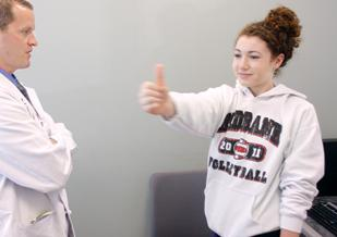 """Michael """"Micky"""" Collins, UPMC's Sports Concussion Program executive director, tests high school basketball player Sarah Gourley."""