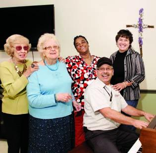 """Catherine Shapiro, far left, and Emily Doublet, residents of Baptist Homes' skilled nursing nursing unit in Mount Lebanon, join employees of the home in a rendition of """"Yankee Doodle."""" Joe Terlecki plays piano and is joined by Leslie Hicks and Amy Angotti. Employees often burst out into song at the facility as a way of relieving stress."""