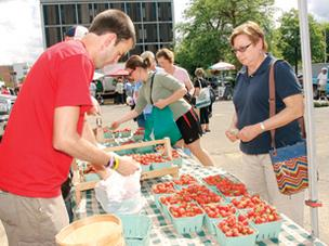 John Karmazin, an employee of Woolf Farms of East Rochester, Ohio, bags strawberries for a customer at the Citiparks Farmers Market in East Liberty.