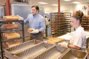 5 Generation Bakers co-owner Scott Baker shelves gourmet cinnamon swirl bread as employee Lisa Woods removes the oven-fresh product from crimp pans.