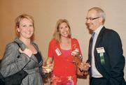 Jackie Ziemianski, left, and Barry Kukovich, both of Peoples Natural Gas, talk with Debbie Frick-Watts of the American Heart Association prior to the Energy Leadership Awards ceremony.