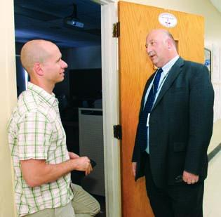Sto-Rox School District Superintendent Michael Panza stops to chat with chemistry teacher Josh Lucas at Sto-Rox High School. The district has faced financial problems in recent years, and 22 district employees, including eight teachers, will either be furloughed or moved to other jobs for the next school year.