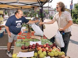 Ed Jodikinos, left, of Jodikinos Farm Market in Clinton, Beaver County, is paid by a customer for produce sold at the South Side Farmer's Market.