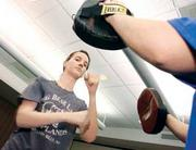 Excela Health Latrobe Hospital ER admissions clerk Tara O'Neal works on  boxing jabs in a boot camp class taught by exercise physiologist Patrick Martin.
