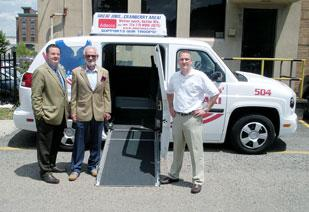 Star Transportation Group President Derek DeLucia, founder Robert DeLucia, and Vice President Boby DeLucia stand outside their Bingham Street office with one of the vehicles being used for the company's Veterans Taxi Service.