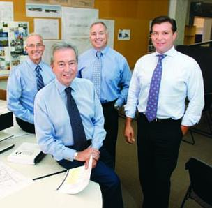 Louis D. Astorino, front, chairman and founder of Astorino, recently passed the reins to his son, Louis P., right, who was named CEO. With them in back are Tim Powers, left, president of architecture, and Robert Ward, president of engineering.