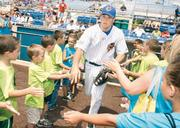 Catcher and former Duquesne University and University of Pittsburgh baseball player Rick Devereaux greets his young fans as he takes the field.