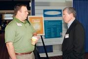 Dan Simonsen, Northwest Savings Bank OGM Division, left, talks with Douglas Hunter, Hunter Brothers International, at the event.