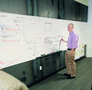 John Crowley, director of business and product design, has a discussion with Lead Designer Katie Scott (not shown) as he writes on a white board at the UPMC Technology Development Center in East Liberty.