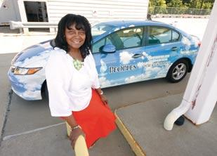 Lutitia Clipper, natural gas vehicle specialist at Peoples Natural Gas, stands next to her company car, a 2012 Honda Civic NGV.