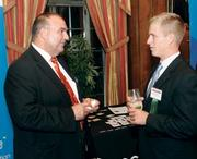 Joe Scuilli of Comcast Business Class, left, chats with Chuck Nettles of Luttner Financial Group Ltd. at the event.