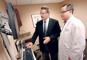 Dr. Kelly Agnew, left, managing partner of Tri Rivers Surgical Associates Inc. and Dr. Benedict Woo look over a digital X-ray image at Tri Rivers' new Mars facility. Tri Rivers continues to expand at a time when independent medical practices are being snapped up by the big hospital networks.